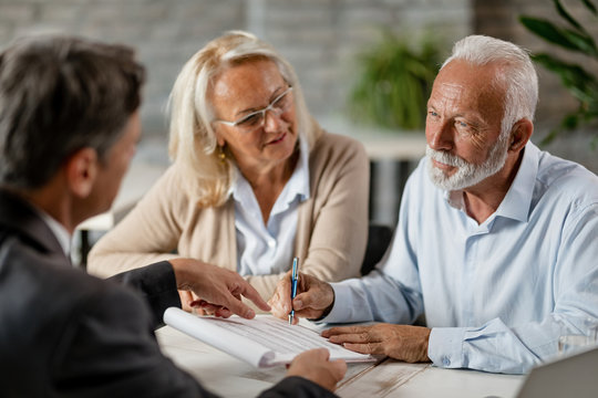 Senior couple signing a contract while having a meeting with insurance agent in the office.