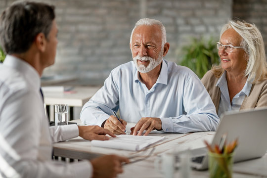Happy senior couple signing an agreement while having a meeting with financial advisor.