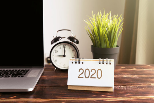 New Year 2020 calendar on office desk with laptop and alarm clock