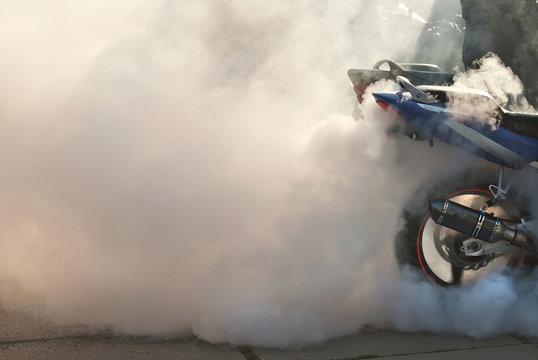 The smoke comes out from under the wheels. Motorcycle wheel closeup. Smoke due to tire rubbing against asphalt. The rider prepares to do the trick on the motorcycle. Burned rubber on the road.