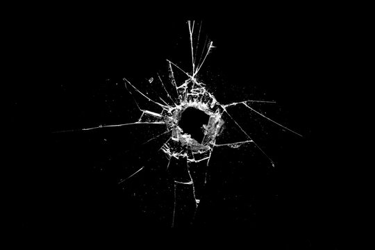 hole in the glass with cracks isolated on a black background