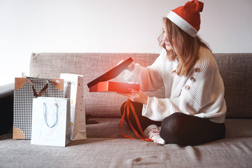 People celebrating xmas love and happiness concept - beauty girl opening present gifts sitting on sofa at home