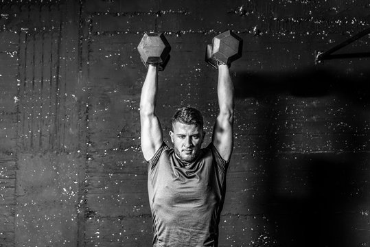 Young strong fit muscular sweaty man with big muscles strength cross workout training with dumbbells weights in the gym dark image with shadows real people black and white