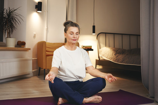 Senior woman in sportswear sitting barefooted on floor at home, keeping legs crossed on mat, doing meditation after yoga practice, having calm peaceful facial expression. Retirement and well being