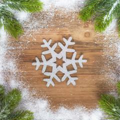 Tannengrün mit Schnee und einem Deko Schneestern auf altem Holz - Weihnachten - Textfreiraum - Vorlage