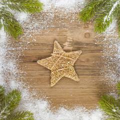 Tannengrün mit Schnee und einem Deko Stern auf altem Holz - Weihnachten - Textfreiraum - Vorlage