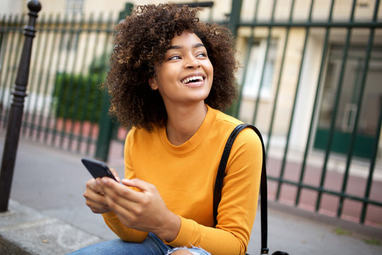 happy african american young woman holding cellphone and looking away