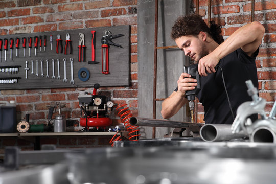 man in home workshop garage work drilling metal with drill, repair iron pipe on the workbench full of wrenches, diy and craft concept