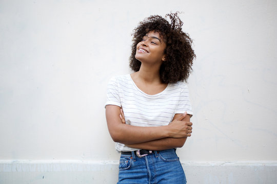 happy young african american woman smiling with arms crossed and looking away against white background