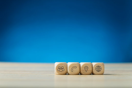 Four wooden dices with contact and information icons on them placed in a row