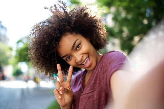 happy african american woman taking selfie with peace hand sign outside