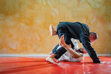 Two brazilian jiu jitsu athletes working on BJJ guard position at the training sparring or drilling fighters at the academy class