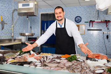 Seller in black apron showing fish on his counter