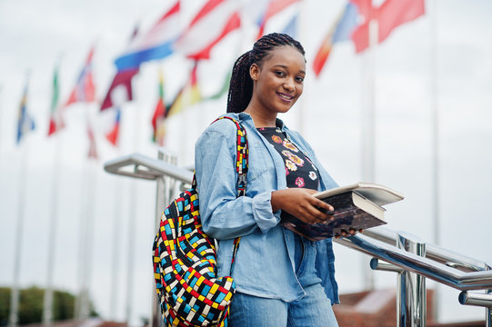 African student female posed with backpack and school items on yard of university, against flags of different countries.