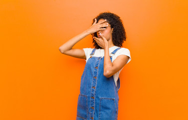 young pretty black woman covering face with both hands saying no to the camera! refusing pictures or forbidding photos against orange wall