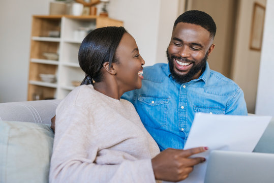 Laughing African American couple doing online banking at home