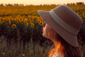 Blurred image of a young girl wearing a hat and looking to the side, beautiful sky bakground. People, travel concept.