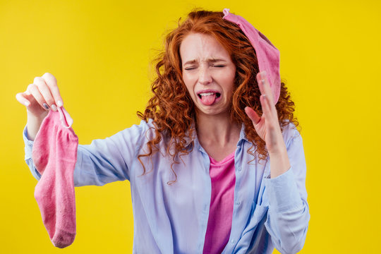 curly ginger redhead woman in a cotton shirt gesture smells bad holding a dirty pink sock out a disgusted look on her face in studio yellow background