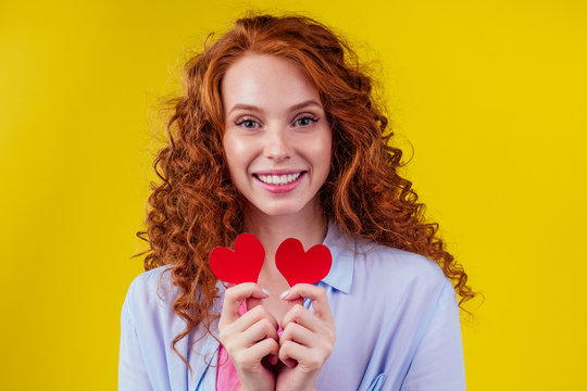sex education concept.redhaired ginger curly woman holding heart paper valentites card in studio yellow background
