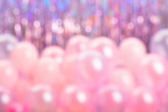 Defocused pink and purple balloons on colorful background.