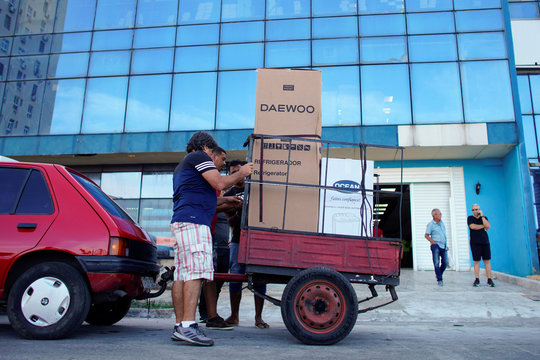 People put into a car trailer a refrigerator and a washing machine just bought from a shop selling products for dollars in Havana
