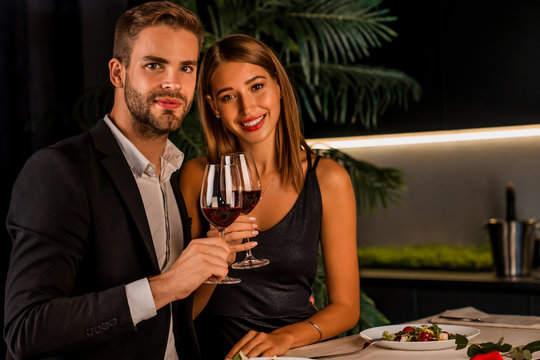 Portrait of happy couple in romantic dinner toasting with wine and looking in camera