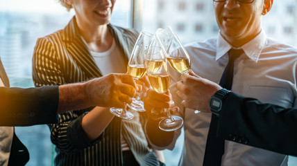 Toasting to success concept.Group of business people toast with champagne and smiling while standing close to each in bar.Friends clinking and toasting with glasses of champagne in lounge.