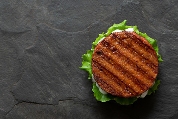 Freshly grilled plant based burger patty on bun with lettuce and sauce isolated on black slate. Top view. Copy space.