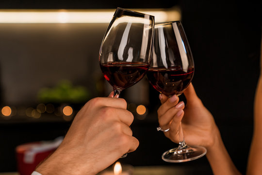 Close up shot of man and woman toasting and drinking red wine from glasses on dinner