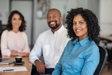 Diverse businesspeople smiling while sitting together at an office table