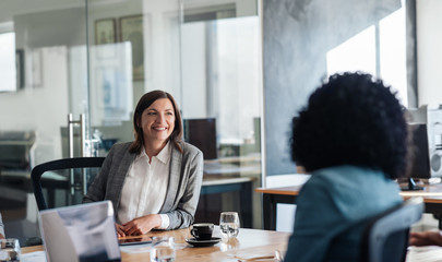 Two smiling businesswoman talking together around an office table