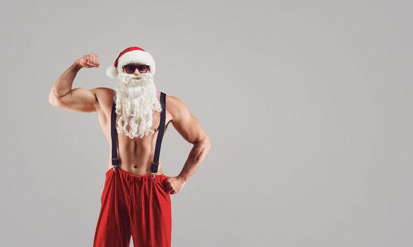 Bodybuilder in sunglasses and Santa suit