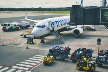 Gdansk / Poland - August 4 2019: Checked freight cargo luggage being driven towards a Ryanair aeroplane on the runway at Gdansk airport
