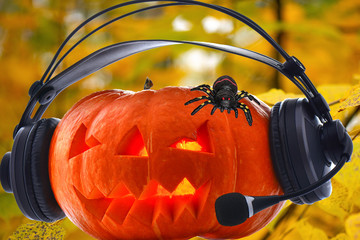 Halloween orange musical pumpkin in headphones with bright glowing eyes and a spider with red beady eyes