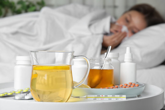 Hot lemon tea with different cold remedies on white table and sick woman on background