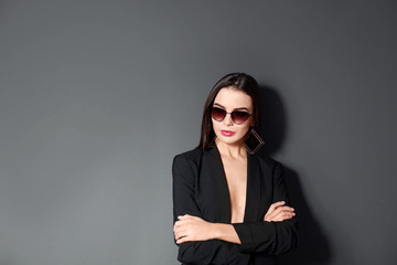 Beautiful woman wearing jacket and sunglasses on black background, space for text Wall mural