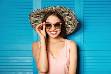 Beautiful woman wearing sunglasses and hat near blue wooden folding screen Wall mural