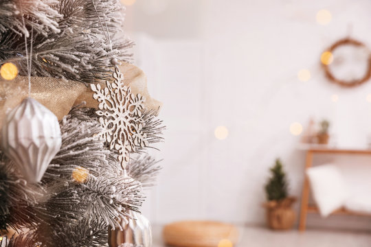 Closeup view of decorated Christmas tree in room, space for text. Festive interior