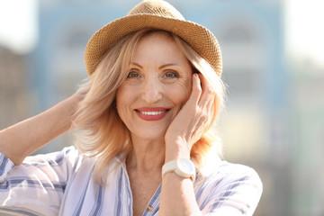 Portrait of happy mature woman on city street