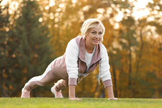 Mature woman doing exercise in park. Active lifestyle