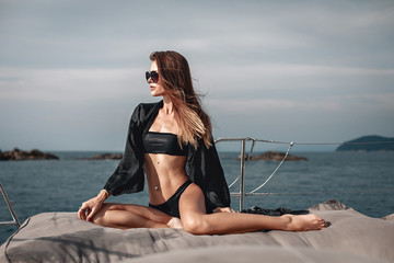 Confident woman in black bikini and sunglasses having wonderful time on the yacht.
