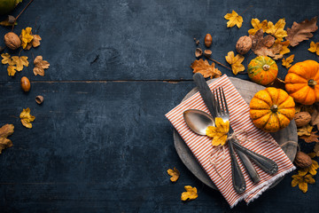 Thanksgiving background with cutlery, pumpkins and dry leaves