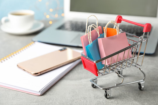 Composition with small shopping cart and paper bags on grey background, space for text