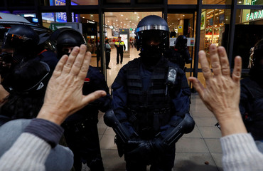 A riot police officer stands guard as people participate in a protest outside the Sants train station in Barcelona