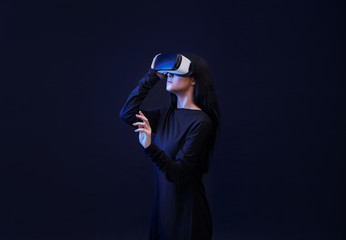 Wall Mural - Woman in VR helmet scrolling invisible screen while interacting with virtual reality under neon light. Girl in glasses of virtual reality. Augmented reality, game concept. Dark background.