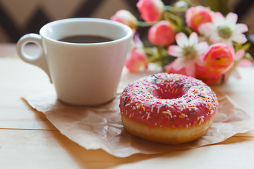 Strawberry donut and coffee cup on the table. Valentine's day concept.