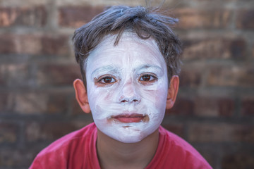 Child with face painted white. Young and charming mime looking at the camera.