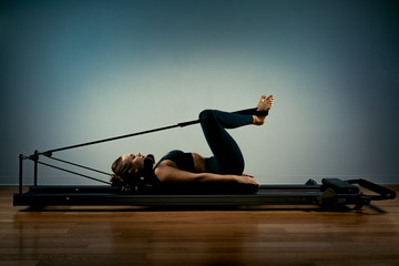 Young girl doing pilates exercises with a reformer bed. Beautiful slim fitness trainer on a...