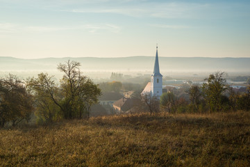 Aluminium Prints Eastern Europe Church in a village in Transylvania, Romania on a misty autumn morning
