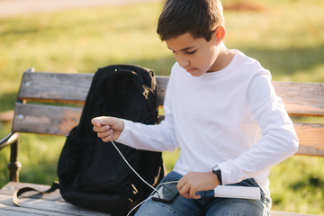 Teenage boy in white shirt use powerbank for charging his smartphone otside. Low battery on...